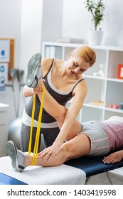 Rehabilitation process. Nice professional therapist working with patient while having rehabilitation therapy
