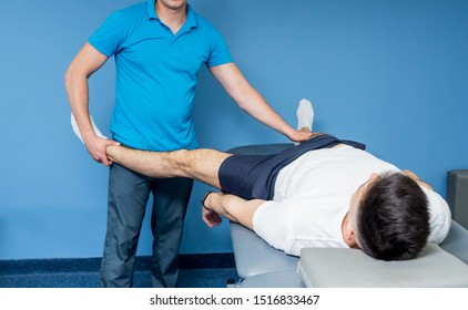 Rehabilitation therapy. Physiotherapist working with young male patient in the rehabilitation center. Treatment pain in spine