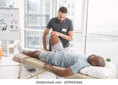 Rehabilitation therapy. Professional male therapist working in the rehabilitation center while doing the therapy