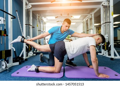 Rehabilitation therapy. Young man doing exercises on mat under supervision of physiotherapist. Treatment pain in spine