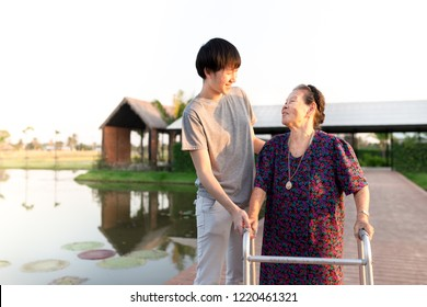 rehabilitation training practice, stroke patient use walker, Asian old female training to use walker with care giver, walk training, family time
