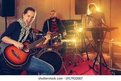 Rehearsal of music band. Young woman guitar player and singer practicing with band members in recording studio