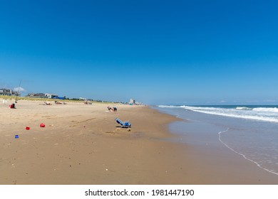 REHOBOTH, DELAWARE - USA - AUGUST 17, 2020: A relatively empty beach south of Rehoboth Beach on a sunny summer afternoon. Empty beach chair in foreground and town of Rehoboth in background.