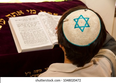 REHOVOT, ISRAEL-JANUARY 19, 2018: A rear view of praying young man pointing at a phrase in a bible book (sefer torah), while reading a pray
