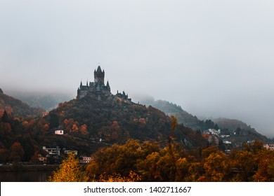 Reichsburg Cochem / Castle Cochem covered in fog with river Mosel during a misty autumn day with low hanging clouds and orange trees (Cochem, Germany, Europe)