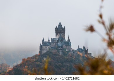 Reichsburg Cochem / Castle Cochem covered in fog during an orange and misty autumn day with low hanging clouds and fog (Cochem, Germany, Europe)