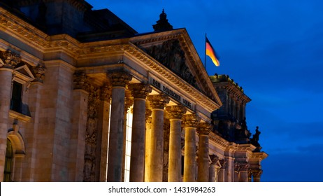 "Reichstag (Deutscher Bundestag) with golden lighting at night. Famous Reichstag building, seat of the German Parliament .Central Berlin Mitte district. Dedication on the frieze ""To the German people""."
