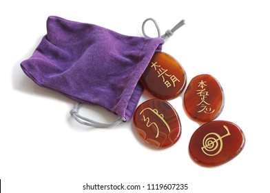 """Reiki Healing Carnelian Stones and Purple Velvet carrying bag on white background - Reiki Meaning: Rei which means """"God's Wisdom or the Higher Power"""" and Ki which is """"life force energy"""""""