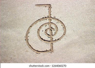 Reiki healing symbol cho ku rei on sand. Alternative medicine concept.
