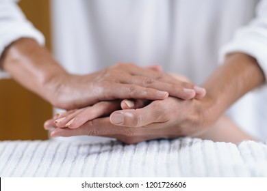 Reiki practitioner and patient holding hands at Reiki session. Energy healing concept.