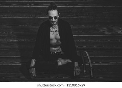Reincarnation and rebirth. Man with tattooed torso in black clothes sitting in meditation pose with swords on wooden floor. Zen, concentration, buddhist concept.