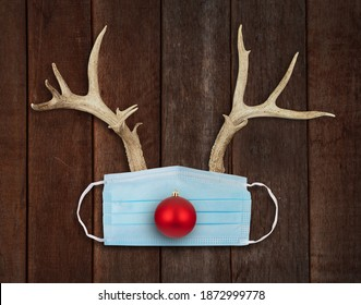 Reindeer Christmas with real animal deer antlers and red bulb ornament.  Rudolph the red-nosed reindeer.  Wooden rustic background.  Face mask.  Medical blue disposable covid-19 mask.