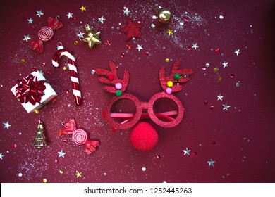 Reindeer face made of Christmas decoration on red background. Flat lay style. Festive concept.
