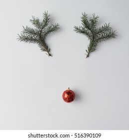 Reindeer face made of Christmas decoration and pine branches. Minimal christmas concept. Flat lay.