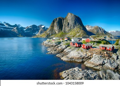 Reine, Lofoten, Norway - 04/06/2017:  The village of Reine under a sunny, blue sky, with the typical red rorbu houses.