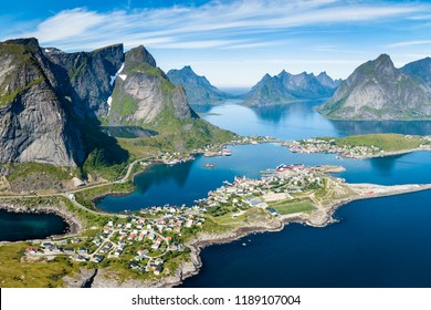 Reine Lofoten Norway, aerial view of Norwegian traditional fishing village above polar circle with blue sea and mountains during sunny arctic summer, famous for Reinebringen hike
