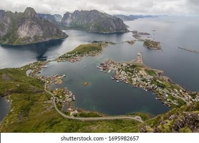 Reine village and ocean from Reinebringen mountain peak in cloudy sky. Reine, Lofoten island, Norway.