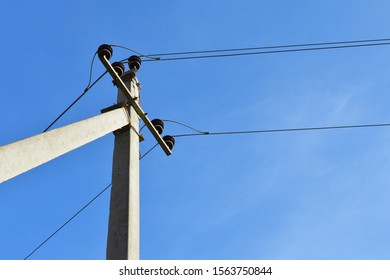 Reinforced concrete electrical support. Electric pole with wires.