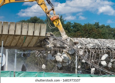 Reinforced concrete road building demolition with use of heavy equipment excavators on catepillars and pneumatic hammer
