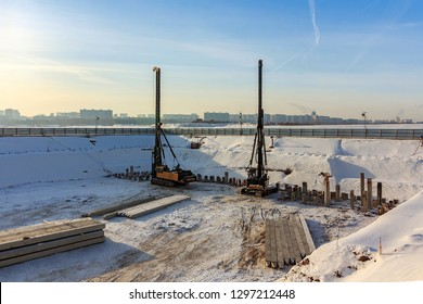 Reinforcement of reinforced concrete piles for foundation on construction site of residential apartment and office building. Installation work at pit in winter on sunny frosty day. Moscow January 2019