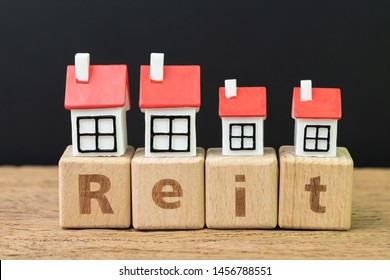 Reit, Real estate investment trust concept, miniature houses on cube wooden block with alphabet combine the word Reit on dark black background.