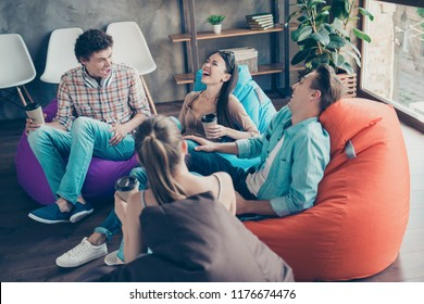 Rejoice and cheerful trandy youths sitting in a loft style room with coffee in hands tell funny stories and humorous joke to each other and aloud laugh without restraint with big toothy smile