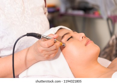Rejuvenating facial therapy treatment at spa salon clinic. Young beautiful Asian woman getting lifting anti-aging, face massage and skincare by electroporation facial therapy aesthetic cosmetology.