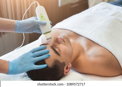 Rejuvenating facial treatment. Man getting lifting therapy massage in a beauty SPA salon. Exfoliation, stimulation and hydratation. Aesthetic cosmetology, closeup, copy space