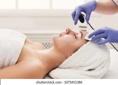 Rejuvenating facial treatment. Model getting lifting therapy massage in a beauty SPA salon. Exfoliation, stimulation and hydratation. Aesthetic cosmetology, closeup, copy space, side view