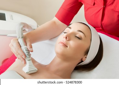 Rejuvenating facial treatment. Model getting lifting therapy massage in a beauty SPA salon. Exfoliation, Rejuvenation And Hydratation. Model and Doctor. Cosmetology.  Close up, selective focus.