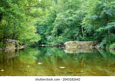 Reka river near Matavun in municipality of Divaca in Littoral region of Slovenia with a reflection of the trees in the river - Shutterstock ID 2043182642
