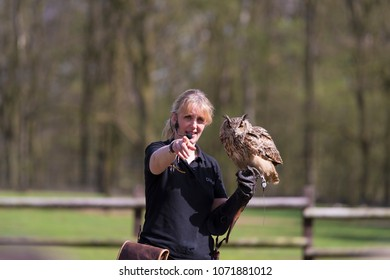 REKE, GERMANY - APRIL 15, 2018: Unknown woman with an owl on her hand giving a show in a local animal park