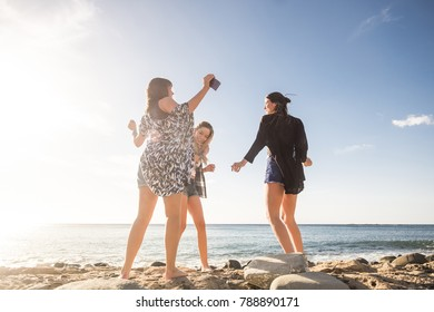 Relationship between three young beauty woman dancing on the beach during a vacation. Sunset time in Tenerife, flare effect and warm filter.