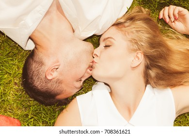 Relationship goals, love forever concept. Man and woman lying on grass and kissing, enjoying spending romantic time together