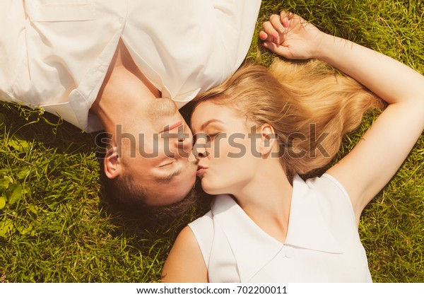 Relationship goals, love forever concept. Man and woman lying on grass having date, enjoying spending romantic time together