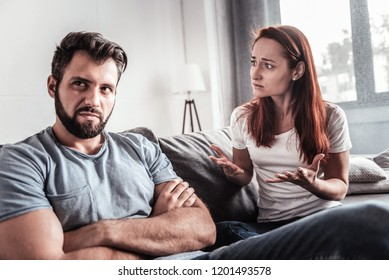 Relationship problems. Cheerless nice young woman sitting on the sofa and looking at the husband while discussing their problems