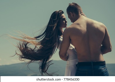 Relationship, romance concept. Couple in love on blue sky. Summer vacation, wanderlust. Man hug woman with long hair on sunny day. Girl and macho with muscular torso on nature.