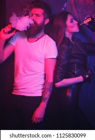 Relationship and vape addiction concept. Couple smoke an electric cigarette on dark and red light room. Brutal bearded man and young pretty woman blowing smoke to join it in one cloud. Couple vaping