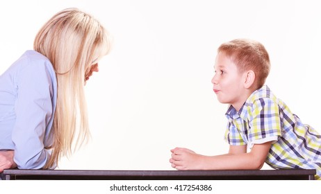 Relationships arguments and discussion. Mother and son sit at table and argue discuss solve problem.