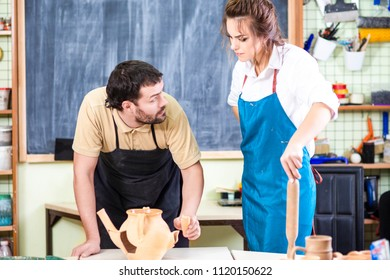 Relationships Issues and Ideas. Caucasian Couple Quarrels in Pottering Workshop. Woman Holding Rolling Pin While Staring at Man With Negative Facial Expression.Horizontal Image