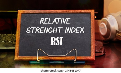 Relative Strength Index RSI words in white color on a black styling board in a wooden frame in the workplace next to the monitor and computer mouse. Financial Concept.
