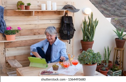 Relax and aperitif time for a caucasian woman using the laptop sitting outdoors in the garden, eating black and green olives and enjoying a red wineglass. Recycled wood on background