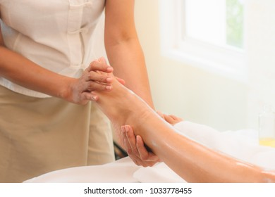 Relax with aroma oil massage in spa salon. woman lying on the bed relaxing with foot massage during treatment in beauty spa.