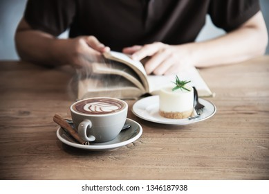 Relax Asian man drink coffee and read book in a modern style coffee shop - people with coffee cup easy lifestyle concept