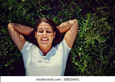 Relax - Beautiful girl lying down in grass, relaxing in the sun. Copy space around her. Click for more: