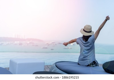 Relax business woman lifestyle at luxury hotel sitting at infinity pool with sea port view sunlight effect in morning. Good life nature vacation concept.