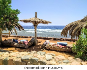 Relax by the sea. Cushions under palm branch umbrellas in Dahab, Egypt.