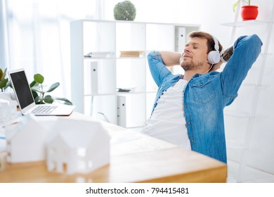 Relax. Calm creative tired engineer sitting at his working place and closing his eyes while listening to pleasant music in his big headphones