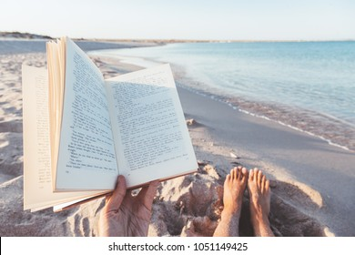 Relax concept. Reading book near the sea - POV. Summer vacations still life. The text is transformed and not recognizable.