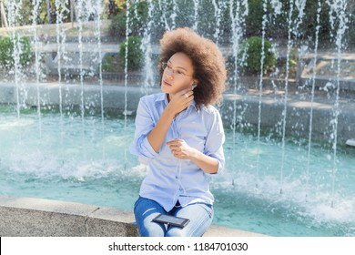 Relax And Enjoy Summer Day, Beautiful Young Afro-American Woman In Casual Wear, Sitting Near Fountain, Listening Music By Earphones